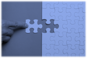An image in blue tones showing a finger inserting last piece of a puzzle